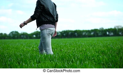 Girl goes on the field of wheat