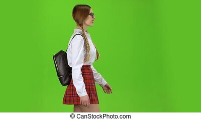 Girl goes straight with a backpack on her shoulders. Green screen. Side view