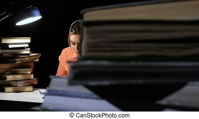 Girl goes through the book and find the right information. Black background