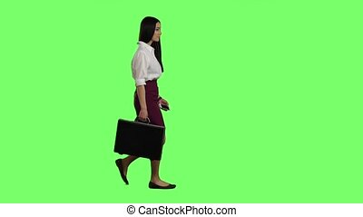 Girl goes to her office and talks on the phone. Green screen. Slow motion