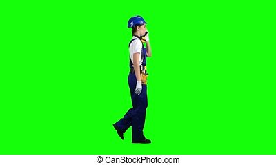 Girl goes to work and speaks on the phone she is an engineer. Green screen. Side view
