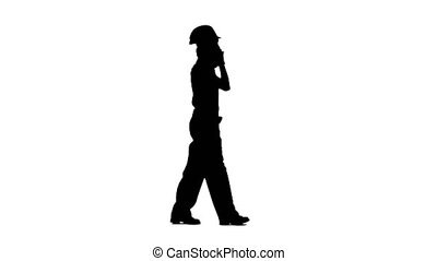 Girl goes to work and speaks on the phone she is an engineer. Silhouette. White background. Side view
