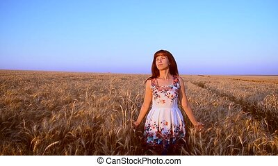 Girl goes with wheat across the field
