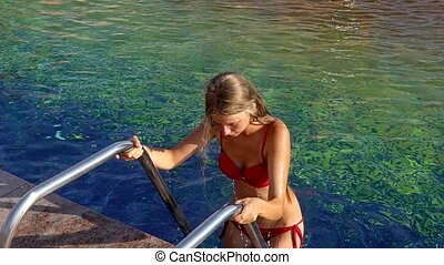 Girl going out swimming pool holding for rails of ladder - ...