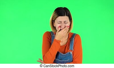 Girl got a cold, sore throat and head, cough on green screen at studio. Brown-eyed girl with an earring in her ear dressed an orange sweater and denim overalls