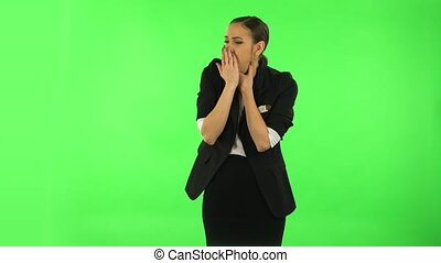 Girl got a cold, sore throat and head, cough. Girl with dark hair wearing a black business suit at green screen at studio.