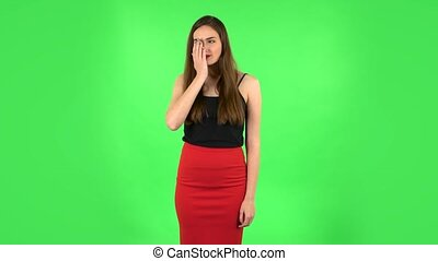Girl got a cold, sore throat and head, cough on green screen at studio. Beautiful brunette with long hair, a gentle makeup in a black tank top and red skirt on a green screen in the studio