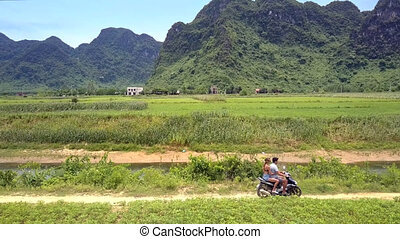 girl guy ride motorbike on path along small river - camera...