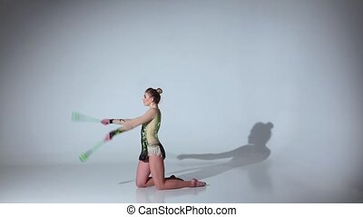 Girl gymnast doing acrobatic movement with a mace in his hand. White background. Slow motion
