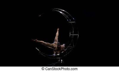 Girl gymnast on one arm performs gymnastic stunts on a rotating structure moon . Black background