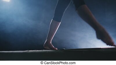 Girl gymnast practicing on a balance beam in gym. - Girl...