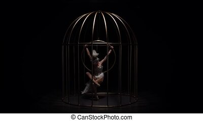 Girl gymnast riding a hoop in a cage on dark stage. Black...
