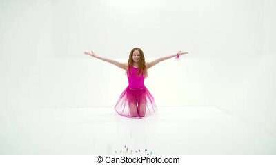 Girl gymnast throws up pink small balls. - A cute little...