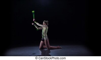 Girl gymnast with mace in hand revolve around him. Black background. Slow motion