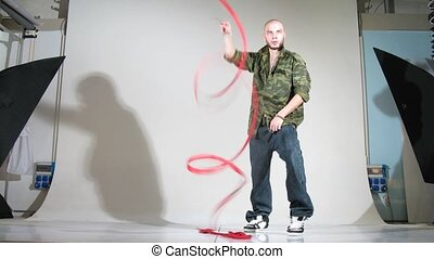 Girl-gymnast with ribbon and rapper pose for photographer in studio