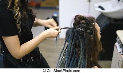 girl hairdresser weaves dreadlocks client in the salon - ...