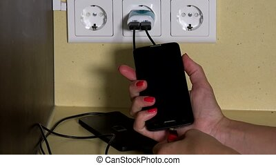 girl hand attach smart phone to wall charger and hold in...