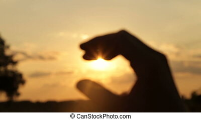 Girl hand closes the sun