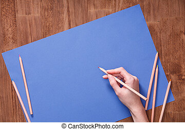 Girl hand drawing, blank blue paper and colorful pencils on wooden table