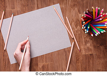 Girl hand drawing, blank grey paper and colorful pencils on wooden table