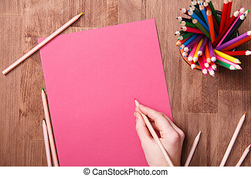 Girl hand drawing, blank pink paper and colorful pencils on wooden table