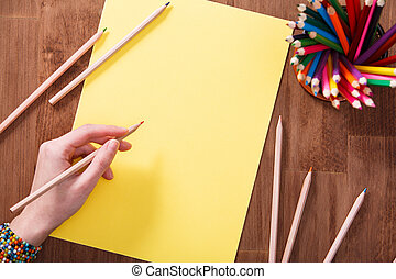 Girl hand drawing, blank yellow paper and colorful pencils on wooden table