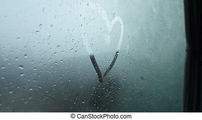 Girl hand draws a heart on a wet window.