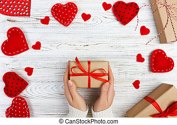 girl hand give valentine gift box with a red heart inside on a white old wooden table. Valentine day