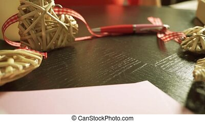 Girl hand putting down an envelope with a red lipstick stamp on it. Close up