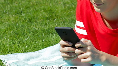 Girl hand texting on phone on the grass - Girl hand texting...