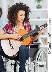 girl handicapped guitarist sitting on wheelchair