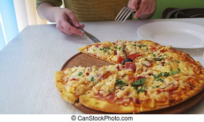 Girl Hands Cut a Slice of Pizza and Put it on a Plate in...