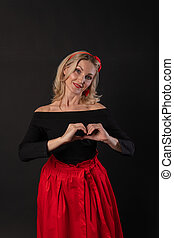 Girl hands hold the heart shape with Valentine's fingers, Valentine's day heart, on the floor hearts space. the formula of art. event, hearts in red dress girl, barefoot