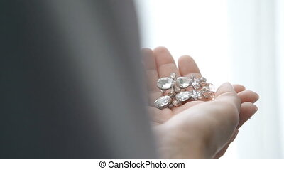 girl hands holding and touching wedding earrings jewellery. ...