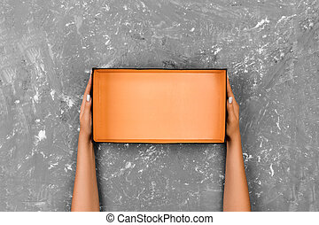 Girl hands holding open empty box on gray background
