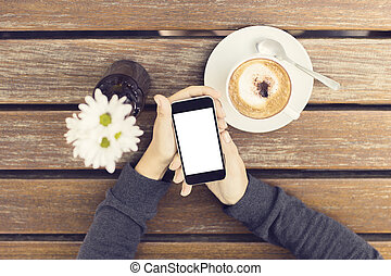 Girl hands with blank smartphone, cup of coffee and flowers on a wooden table