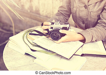 Girl hands with old style camera and books outdoor