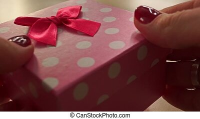 Girl hands with red manicure place pink and white polka dot gift box on table