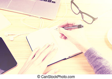 Girl hands writing in the diary with cell phone, glasses and laptop
