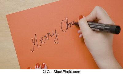 Girl hands writing merry christmas on a red paper card with...