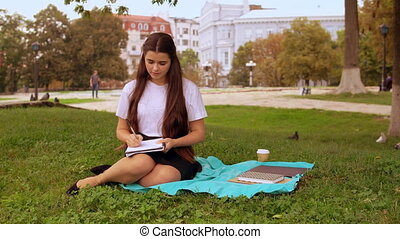 girl handwriting in park - caucasian student writing in...