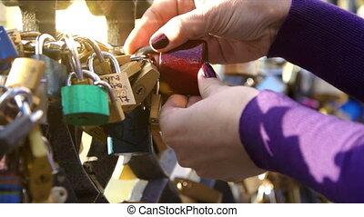Girl hang a padlock of love - Girl (woman) hang a padlock of...