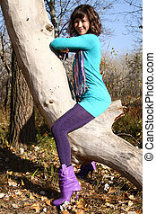 Girl hanging on the tree in an autumn park
