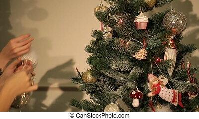 girl hangs on a beautiful Christmas tree toy