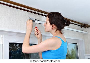 Girl hangs vertical blinds, tighten with a screwdriver, ...