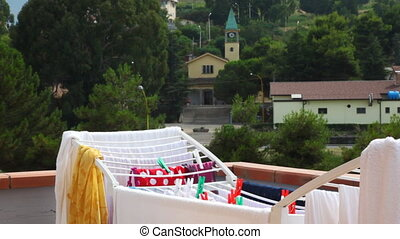 Girl hangs washed clothes to dry at balcony