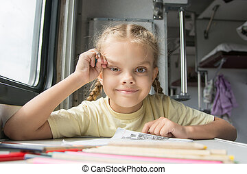 Girl happily looks into the frame, drawing pencils in a train