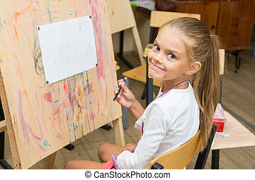 Girl happily looks into the frame on a drawing lesson