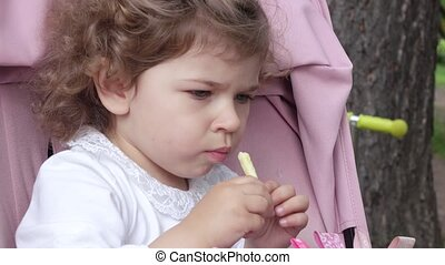 Girl has fried potatoes - Sitting in a baby carriage, the...