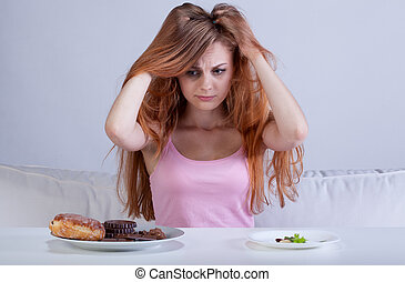 Girl has had enough diet near table